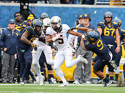 Oct 28, 2017; Morgantown, WV, USA; Oklahoma State Cowboys running back Justice Hill (5) stiff arms West Virginia Mountaineers safety Jovanni Stewart (9) during the first quarter at Milan Puskar Stadium. Mandatory Credit: Ben Queen-USA TODAY Sports