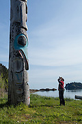 A guest from the National Geographic Sea Lion photographs a totem pole in front of the Haida Heritage Center in Queen Charlotte City, Haida Gwaii.
