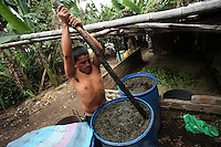 A worker mixes a barrel full of coca leaf and gasoline in one stage of the process of turning coca leaf into coca paste in a remote area of the southern Colombian state of Nariño, on Monday, June 25, 2007. (Photo/Scott Dalton)