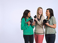 Three young women holding digital cameras studio shot