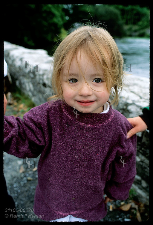 Little girl looks up at camera as she poses for picture in village of Cong. Ireland