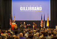Hempstead New York, October 5, 2018. On stage, left, U.S. Senator KIRSTEN GILLIBRAND (D-NY) has Q&A during Town Hall Meeting at Hofstra University. At right is Dean MEENA BOSE, the moderator. Standing at left, audience member asks immigration question.