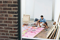 Couple reclining by painting on floor of studio view through window