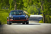 Image of a man driving a black german real 1973 Porsche 911 RS Carrera on a country road in California, model and property released
