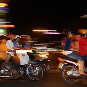 Scooters with passengers of all ages cruise the streets of Dong Khoi in Ho Chi Minh City, Vietnam. Weekends and public holidays sees the streets teaming with scooters and motorbikes, sometimes with all the family on board as they tour the city dressed to impress as they sightsee the city. Dong Khoi, Ho Chi Minh City, Vietnam. 3rd March 2012. Photo Tim Clayton