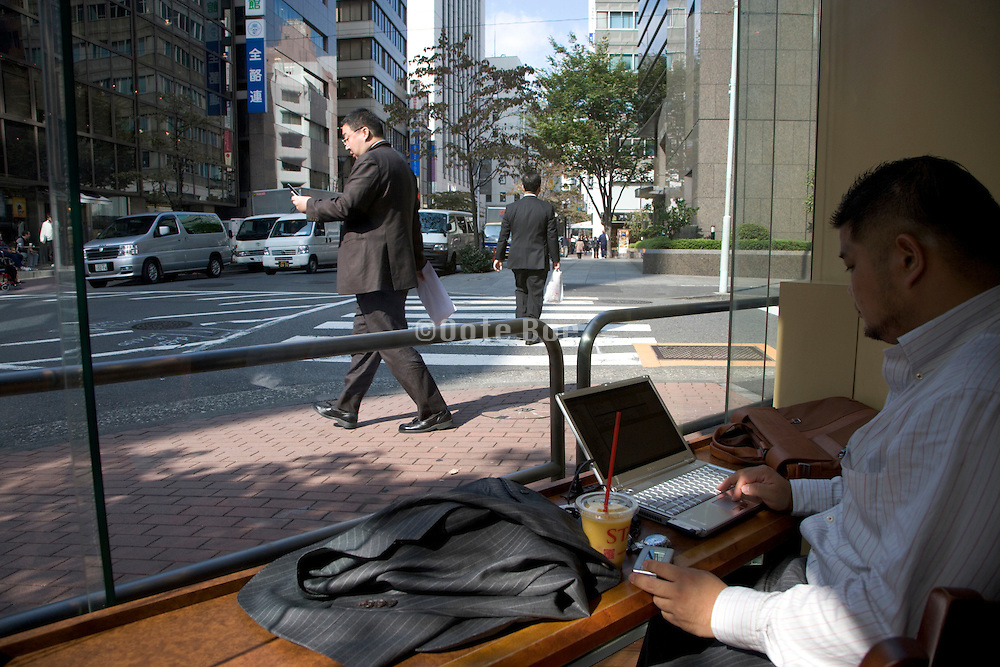 business man working on his laptop while taking a break in a coffee bar Tokyo Japan Ginza district