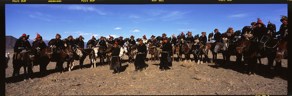 Mongolia. hunting with Eagle. Golden eagle festival in Kazakh province.  Bayan Ulgi.  The tournament participants come from all over Bayan Ulgii province in the extreme west of , near the Kazaksthan border. They arrive dressed in colorful apparel, fur coats and headgear made from wolfskins. Each trainer carries a hooded eagle on their forearm, it's claws firmly planted in a leather glove or  - bialai.  /  chasse à l'aigle  . festival des chasseurs avec Aigle doree, province Kazakh  Bayan Ulgi  Mongolie  .les particiapnts aux tournois arrivent de toute la province de Bayan Ulgii a l'extreme ouest de la Mongolie pres de la frontière avec le Kazaksthan. les chevaux s'abbreuvent dans la rivière Ulgii.  Les cavaliers sont sur leur trente et un : habits d'apparat, dehls multicolores, manteaux de peaux, et chapeaux en fourrure de loup. Chacun tient un aigle encapuchonné, serres plantées dans un gant de cuir (le bialai), posé sur l'avant bras. Ce dernier est en appui sur un bâton sculpté arrimé à la selle. De l'autre, et d'une main, le cavalier tient les rênes