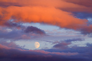 The moon shines through a break in the storm clouds over Mount Douglas on Vancouver Island, Canada.