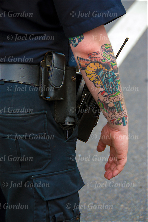 NYPD police officer wearing short sleeves uniform with tattoo &quot;Death or Glory&quot; on his arm. <br /> <br /> Officer is grandfathered joined the police force before 2007. After 2007 he would have to cover up his tattoos.  His assignment that day was to cover crowd control for a march / demonstration in Greenwich Village during Gay Pride Weekend.