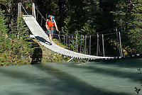 Hiker crossing suspension bridge over Helmet Creek, Kootenay National Park British Columbia Canada