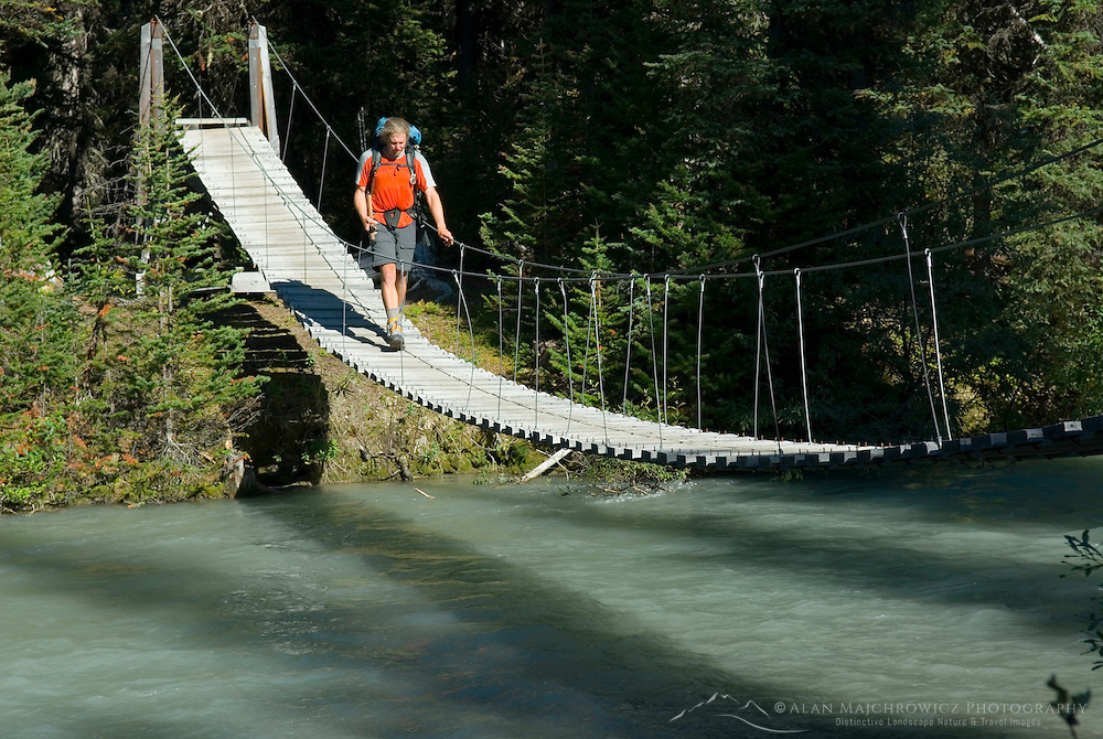 Hiker crossing suspension bridge over Helmet Creek, Kootenay National Park British Columbia Canada
