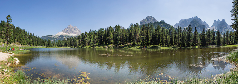 "Lago Antorno, Tre Cime/Drei Zinnen Nature Reserve, in the Province of Belluno, Veneto region, postal code 32040 Misurina Tre Cime di Lavaredo, Italy. At left rise the pyramids of Tre Cime di Lavaredo (Italian for ""Three Peaks of Lavaredo,"" called Drei Zinnen or ""Three Merlons"" in German). In the Cadini di Misurina at right, Cima Grande rises to 2999 meters (9839 feet). The Cadini Group is in the Sesto Dolomites (Dolomiti di Sesto, or Sexten/Sextner/Sextener Dolomiten) which lie north of the Fiume Ansiei valley, in the municipality of Auronzo. The Dolomites are part of the Southern Limestone Alps, in northern Italy, Europe. UNESCO honored the Dolomites as a natural World Heritage Site in 2009. This panorama was stitched from 8 overlapping photos."