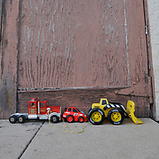 Child's toy trucks arranged on concrete driveway against weathered, red-toned, old garage door.