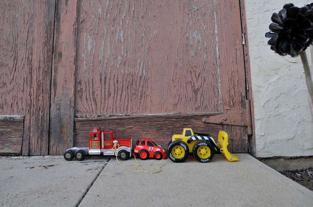 Childs Toy Trucks Against Old Weathered Garage Door Harrison