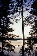 A canoe with 2 paddlers at sunset on Millinocket Lake, near Baxter State Park Maine