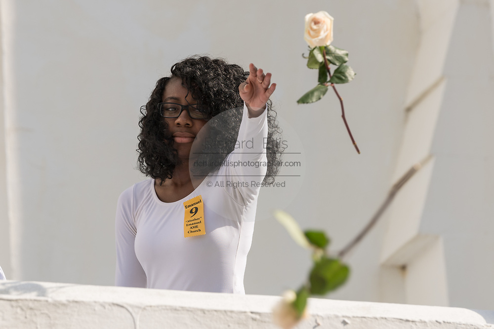 Young members of the praise dance group of the Mother Emanuel African Methodist Episcopal Church throw roses from the church during a ceremony marking the 2nd anniversary of the mass shooting June 17, 2017 in Charleston, South Carolina. Nine members of the historic African-American church were gunned down by a white supremacist during bible study on June 17, 2015.