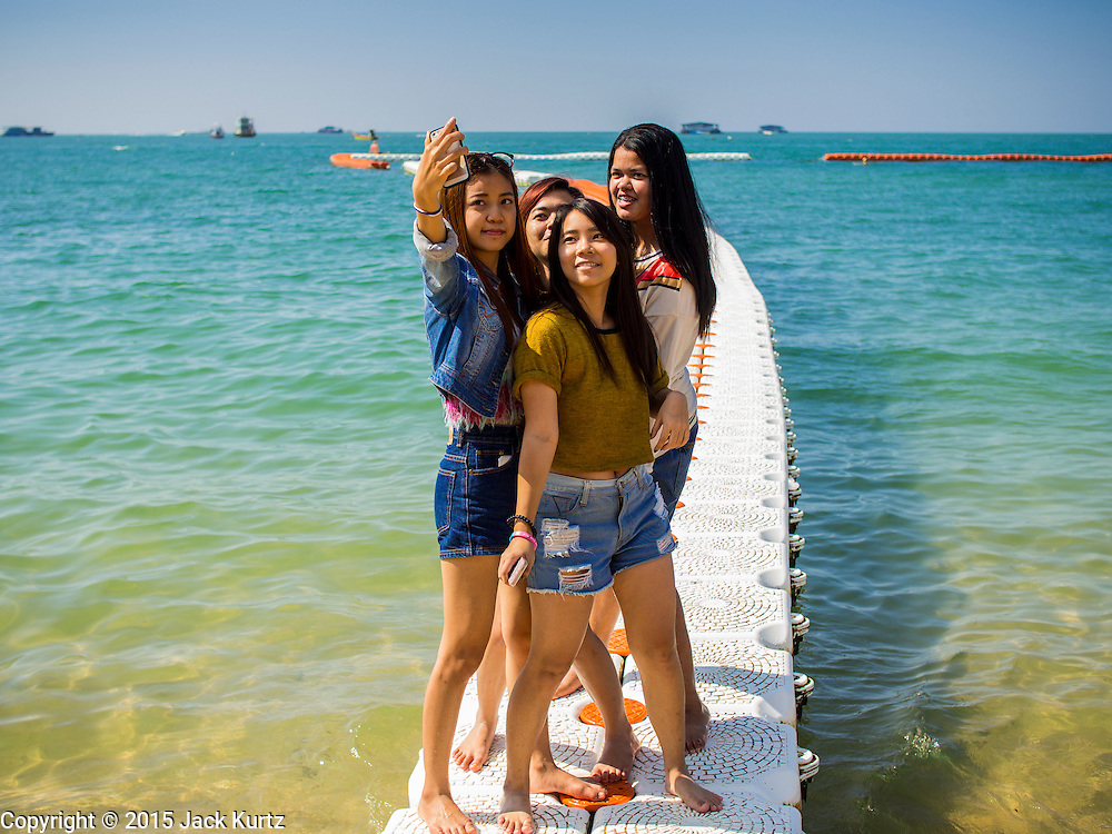 06 JANUARY 2015 - PATTAYA, CHONBURI, THAILAND: Thai women take selfies on Pattaya beach. The Thai government has announced plans to clean up Pattaya beach, one of the most famous beaches in Thailand. Pattaya is about 2.5 hours from Bangkok. They plan to reduce the number of umbrella and chaise lounge vendors on the beach and regulate the personal watercraft and parasailing vendors on the beach. The government has already cleaned up beaches on Phuket island and Hua Hin.    PHOTO BY JACK KURTZ