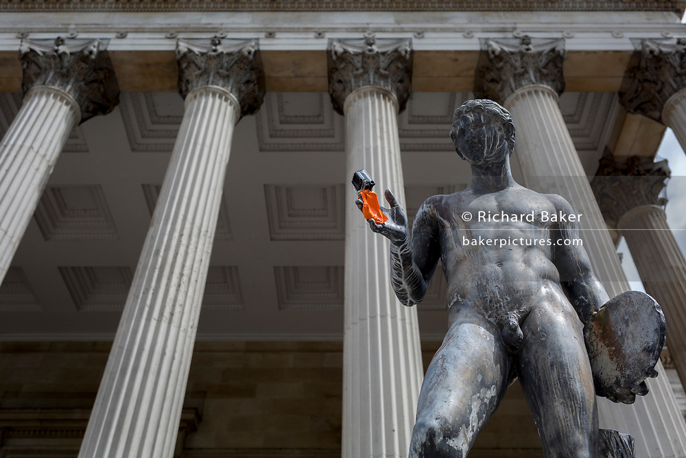 A classical statue with a GoPro camera taped to one hand stands beneath Corinthian columns of the Main Building at University College London (UCL), on 3rd August 2017, in London, England.