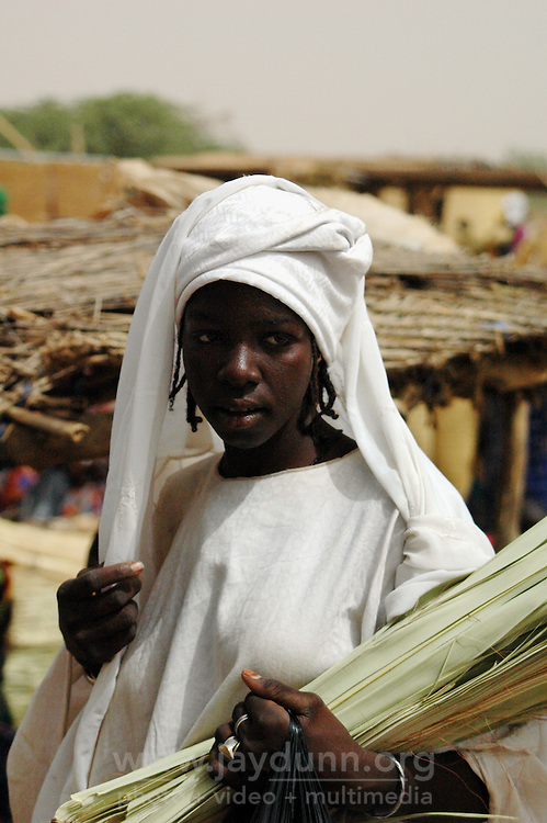 BURKINA FASO, Gorom-Gorom, 2007. This young woman is selling reeds for weaving baskets at Gorom-Gorom's busy Thursday market.