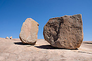 "Boulders erode and split from the top of Enchanted Rock. Explore a large pink granite dome at Enchanted Rock State Natural Area, between Fredericksburg and Llano, Texas, USA. Enchanted Rock is a fascinating exfoliation dome (with layers like an onion), rising 425 feet (130 m) above its surroundings to elevation of 1825 feet (556 m) above sea level, in the Llano Uplift. Geologically, the exposed rock (monadnock or inselberg, ""island mountain"") is part of a pluton (bubble of rock slowly crystallized from magma) within the billion-year-old igneous batholith, Town Mountain Granite (covering 62 square miles mostly underground), which intruded from a deep pool of hot magma 7 miles upwards into the older metamorphic Packsaddle Schist. The overlying sedimentary rock (Cretaceous Edwards limestone) eroded away to expose the prominent domes seen today: Enchanted Rock, Little Rock, Turkey Peak, Freshman Mountain, and Buzzard's Roost."