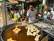 12 OCTOBER 2015 - BANGKOK, THAILAND: A Chinese donut vendor fries up dough in his stand on Yaowarat Road on the first day of the Vegetarian Festival in Bangkok's Chinatown. The Vegetarian Festival is celebrated throughout Thailand. It is the Thai version of the The Nine Emperor Gods Festival, a nine-day Taoist celebration beginning on the eve of 9th lunar month of the Chinese calendar. During a period of nine days, those who are participating in the festival dress all in white and abstain from eating meat, poultry, seafood, and dairy products. Vendors and proprietors of restaurants indicate that vegetarian food is for sale by putting a yellow flag out with Thai characters for meatless written on it in red.       PHOTO BY JACK KURTZ
