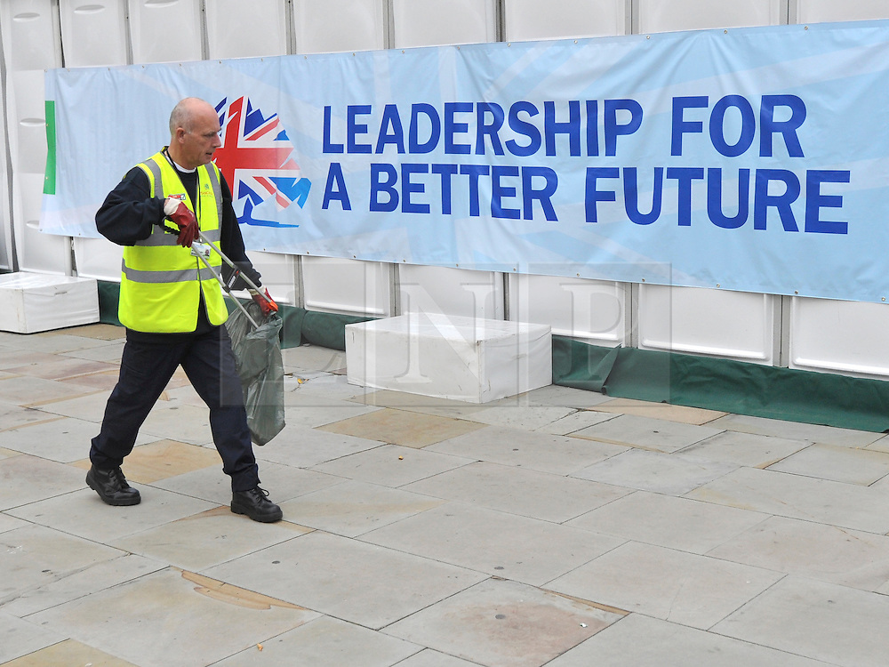 © Licensed to London News Pictures. 05/10/2011. MANCHESTER. UK. A street cleaner works in front of a Conservative Party banner at The Conservative Party Conference at Manchester Central today, October 5, 2011. Photo credit:  Stephen Simpson/LNP