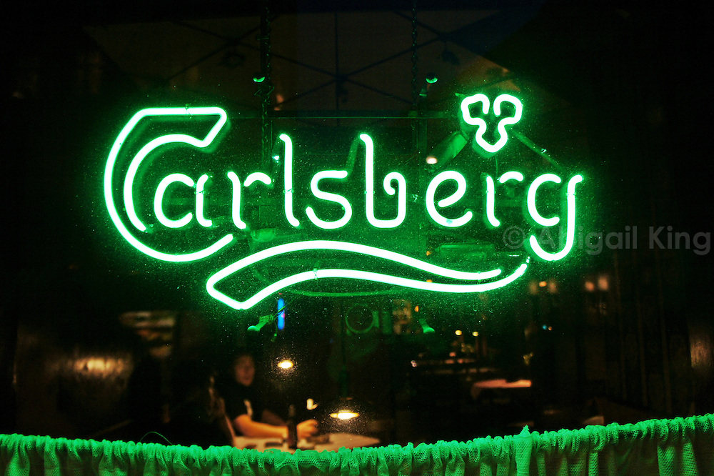 Illuminated green Carlsberg sign in the window of a pub or bar in Copenhagen, Denmark.