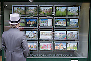 © Licensed to London News Pictures. 18/06/2014. Ascot, UK. A man looks in an estate agents window. Day two at Royal Ascot 18th June 2014. Royal Ascot has established itself as a national institution and the centrepiece of the British social calendar as well as being a stage for the best racehorses in the world. Photo credit : Stephen Simpson/LNP