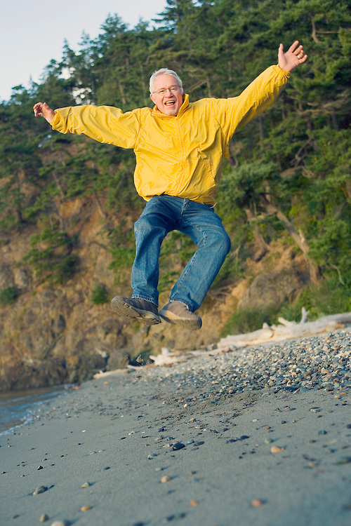 Portrait of senior man clicking heels in midair on beach.