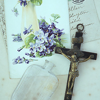 Ebony and brass crucifix lying on antique paper with perfume bottle and old postcards including image of violets