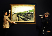 © Licensed to London News Pictures. 02/02/2012, London, UK. A photographer photographs a gallery assistant holding Bernard Buffet's Le Pont de Fer, environs de Saint-Cast. The painting is expected to fetch 25,000-35,000GBP. Photo call at Bonhams, London for Impressionist and Modern Art Auction preview..  Photo credit : Stephen Simpson/LNP