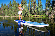 A woman riding the Stand Up Paddle Board on the North Fork of the Payette River near Payette Lake and the city of McCall in the Salmon River Mountains of central Idaho