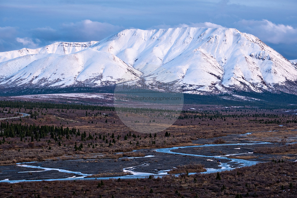 An early season snow dusts the Alaskan Range of mountains behind the Teklanika River in Denali National Park, McKinley Park, Alaska