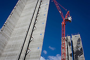 Lift shafts with their floors marked vertically at 5 Broadgate, designed by Make Architects which will become the new home of UBS in London when fully occupied. 700,000 sq feet (66,890 sq m). Rising towards the blue sky is the tower-like structure with blue numbers of future storeys, stencilled on to the grey reinforced concrete. There will be 12 floors to this office complex of 700,000 sq feet (66,890 sq m), scheduled to be completed in 2016. The City of London is the capital's historic centre first occupied by the Romans then expanded during following centuries until today, it has a resident population of under 10,000 but a daily working population of 311,000.