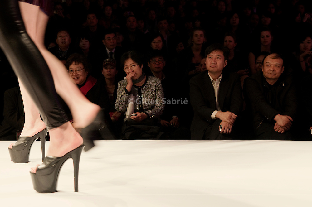 At the opening fashion show of Beijing 2009 Fashion week, a model is going down the catwalk as guests look on.