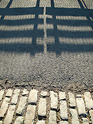 Shadows of a park bench on the pavement being cast from the early morning sun in Central Park, New York City.