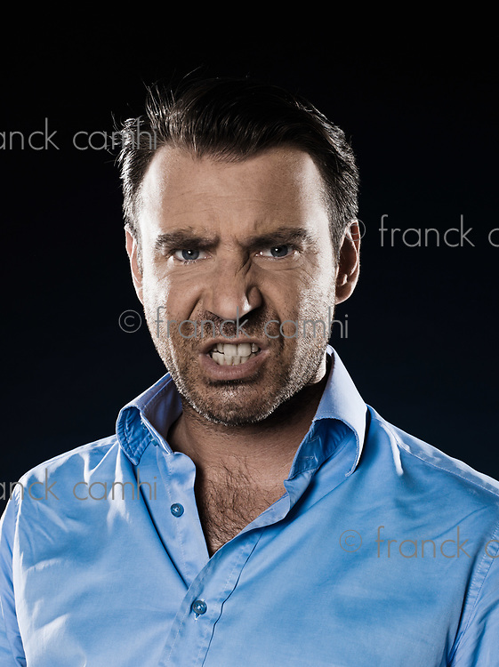 caucasian man unshaven pucker anger portrait isolated studio on black background