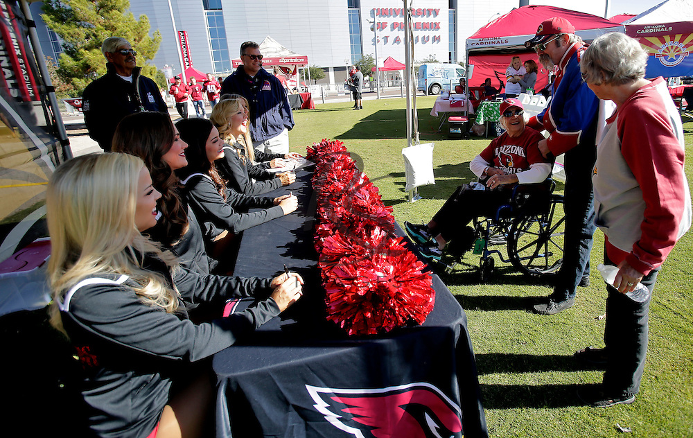 Fans get Arizona Cardinals cheerleaders autographs prior to an NFL football game between the Washington Redskins and the Arizona Cardinals, Sunday, Dec. 4, 2016, in Glendale, Ariz. (AP Photo/Rick Scuteri)