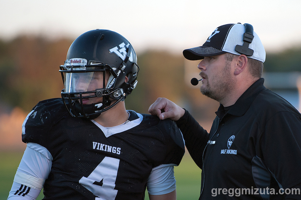 Vale head coach talks to sophomore quarterback Cade Perry. Vale - Burns football game, September 18, 2015 at Vale High School, Vale, Oregon. Vale won 65-28.