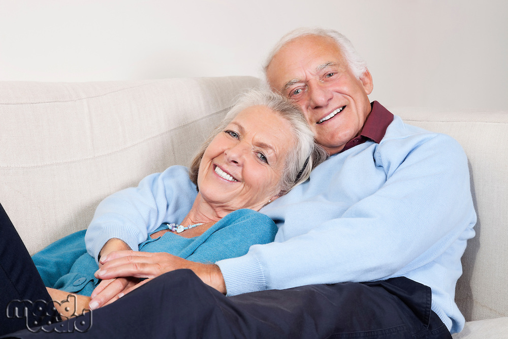 Portrait of happy elderly man with arm around spouse lying on sofa at home