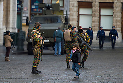 "© Licensed to London News Pictures. 23/11/2015. Brussels, Belgium.  A young girl walks past Belgian military  in The Grand Place, the main square in central Brussels where the city is currently on lockdown amid ""imminent threat"" of Paris-style bomb and gun attacks. Some public transport and schools have been closed as a precaution. Photo credit: Ben Cawthra/LNP"