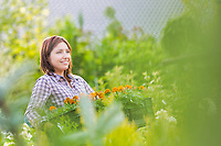 Portrait of mature female gardener carrying flowers in crate at shop