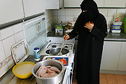 A mother in Dubai cooks her family's lunch in their new kitchen building that is separate from the rest of the house. Her hands are adorned with henna in honor of the wedding she will attend this afternoon. She is covered from head to toe in her home today, as she is when out in public because she is entertaining guests from outside her family. As an indigenous citizen of the United Arab Emirates her family is entitled to a substantial subsidy from the government and jobs for the males in the household. Their high standard of living is a far cry from her parents' life as nomadic Bedouin camel herders of the desert. Dubai, United Arab Emirates. (From a photographic gallery of images of kitchen images, in Hungry Planet: What the World Eats, p. 54) (MODEL RELEASED IMAGE).