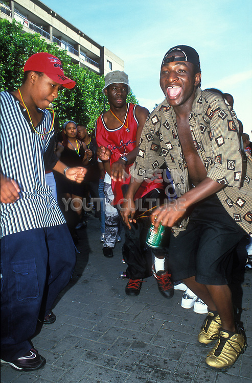 Guys wearing Nike trainers dancing in the street, Notting Hill Carnival, UK 2000