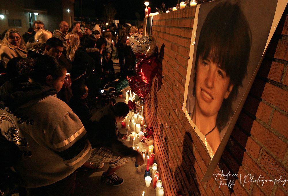 /Andrew Foulk/ For the North County Times/  .Mourners place candles near a photo of Amber Dubois during a Vigil to remember the fourteen year old at Escondido High School Monday night.