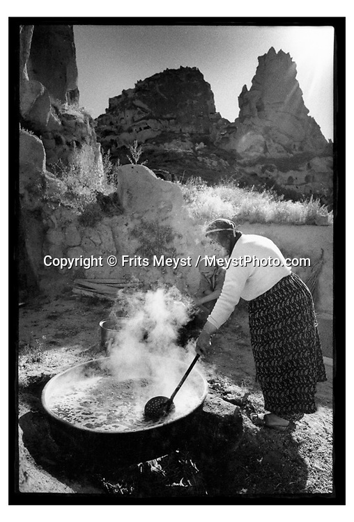 Uchisar, CAPPADOCIA, TURKEY, 2000.  A woman boiles grape juice down to pekmez the local grape syrup.  Traditional life in Cappadocia has come under heavy strain, due to the increased tourism. the young generation is not interested in working the fields if they can work in a carpetshop, restaurant or bar. Therefore centuries old skills and habits will die with the elderly. Cappadocia is knowns for its landscape with conical shaped rock formations and cave dwellings in which the local people live. ©Photo by Frits Meyst/Adventure4ever.com