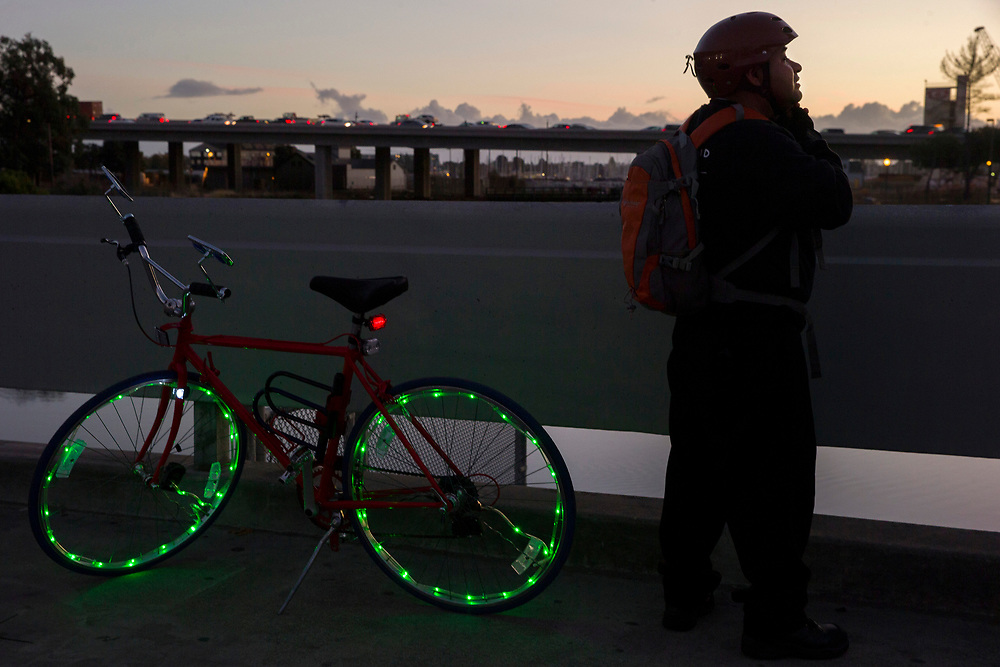 After watching the sunset next to the Peralta Colleges headquarters on East 8th Street, Fernando Lucas puts on his helmet to get back on his bike and ride home, Friday, Nov. 10, 2017, in Oakland, Calif. The Oakland A's are proposing a new stadium at the Peralta Community College District headquarters near Laney College.