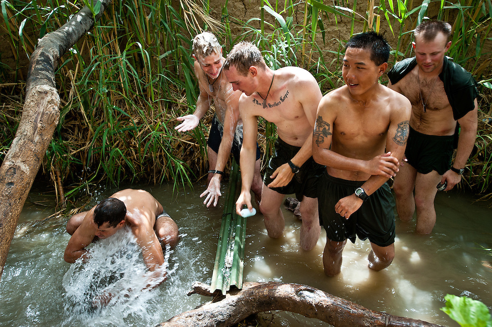 U.S. Marines bathe in an irrigation canal running through their sequestered compound, Patrol Base McElhinney. The Marine patrol bases in Marjah were often cut off from running water and electricity.