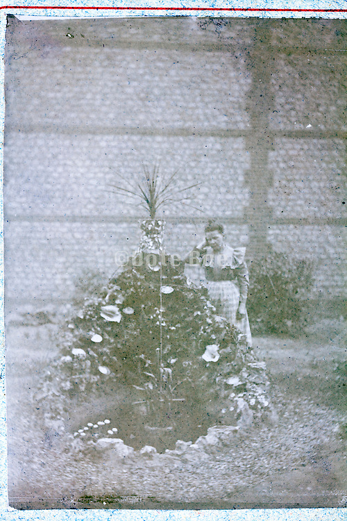 deteriorating photo of woman posing by a decorative flower and plant fountain well