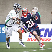 Will Mangan #21 of the Boston Cannons keeps the ball away from Dan Burns #4 of the Chesapeake Bayhawks during the game at Harvard Stadium on April 27, 2014 in Boston, Massachusetts. (Photo by Elan Kawesch)